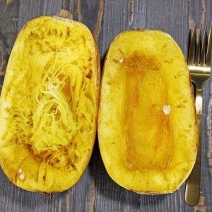 Two halves of roasted spaghetti squash, one with the interior scraped to show the strands