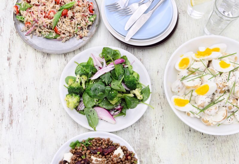 Overhead view of a variety assortment of side dishes, green salad, brown rice salad, lentil beetroot salad on a rustic background